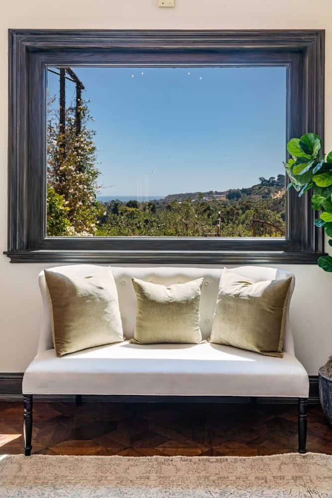 A look at a white couch set near the large glass window overlooking the beautiful surroundings. Images courtesy of Toptenrealestatedeals.com.