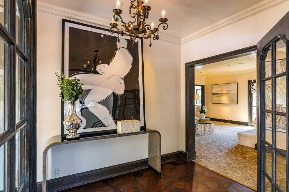 Here's an entry hall leading to one of the rooms. The hall ends with a nice table and a large and artistic wall decor. Images courtesy of Toptenrealestatedeals.com.
