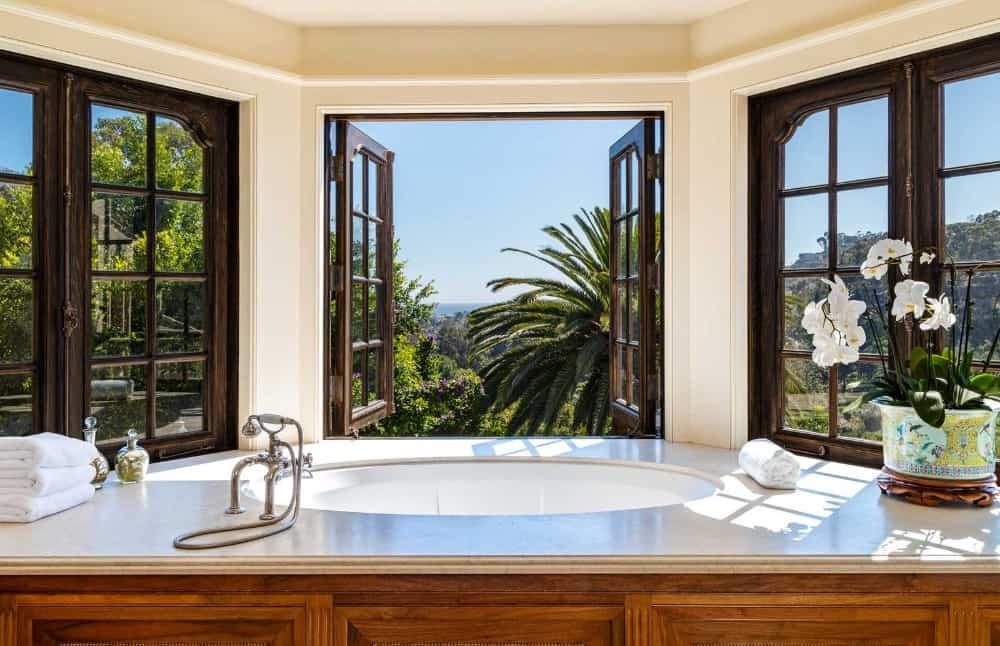 A closer look at the primary bathroom's drop-in soaking tub by the windows providing a gorgeous view of the surroundings. Images courtesy of Toptenrealestatedeals.com.