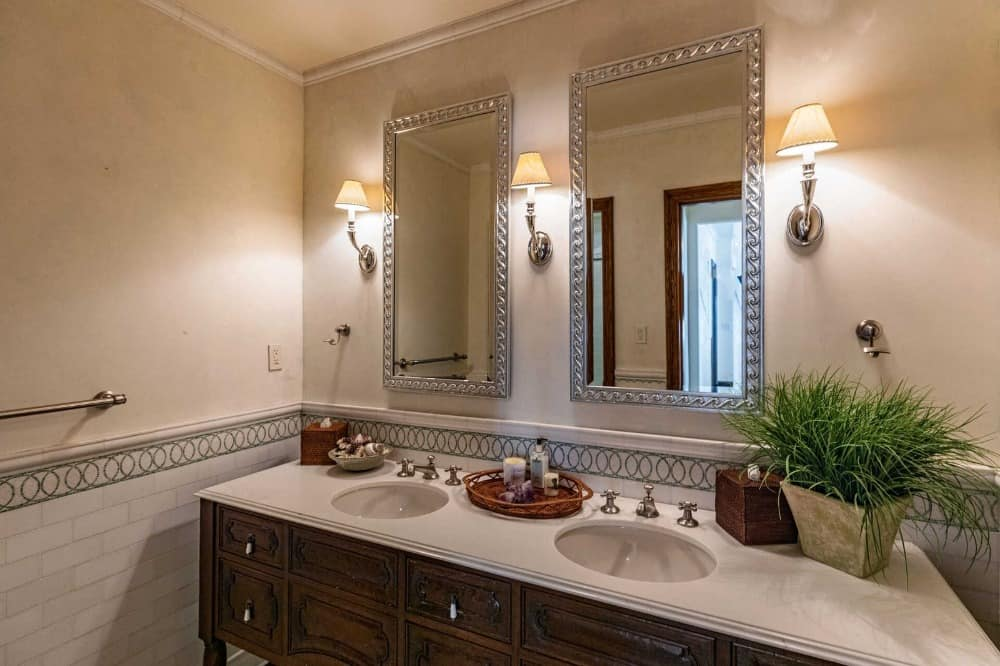 The bathroom offers a double sink on a single sink counter lighted by classy wall lights with two mirrors. Images courtesy of Toptenrealestatedeals.com.