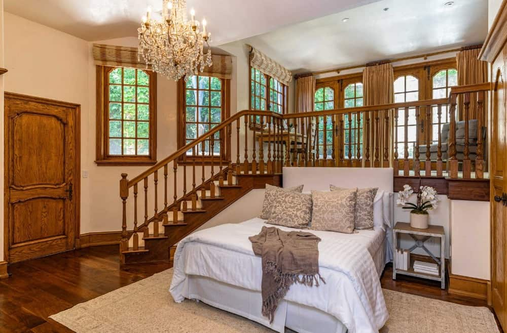 This guests room offers a short staircase to the upper floor of the room where there's a study desk and a sitting chair on the side. Images courtesy of Toptenrealestatedeals.com.