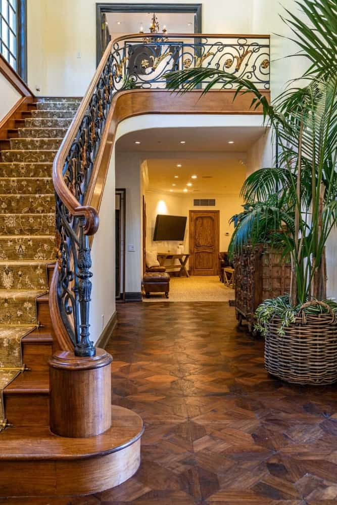 The foyer offers a classy staircase with carpeted steps and stylish hardwood flooring along with a two-storey ceiling. Images courtesy of Toptenrealestatedeals.com.