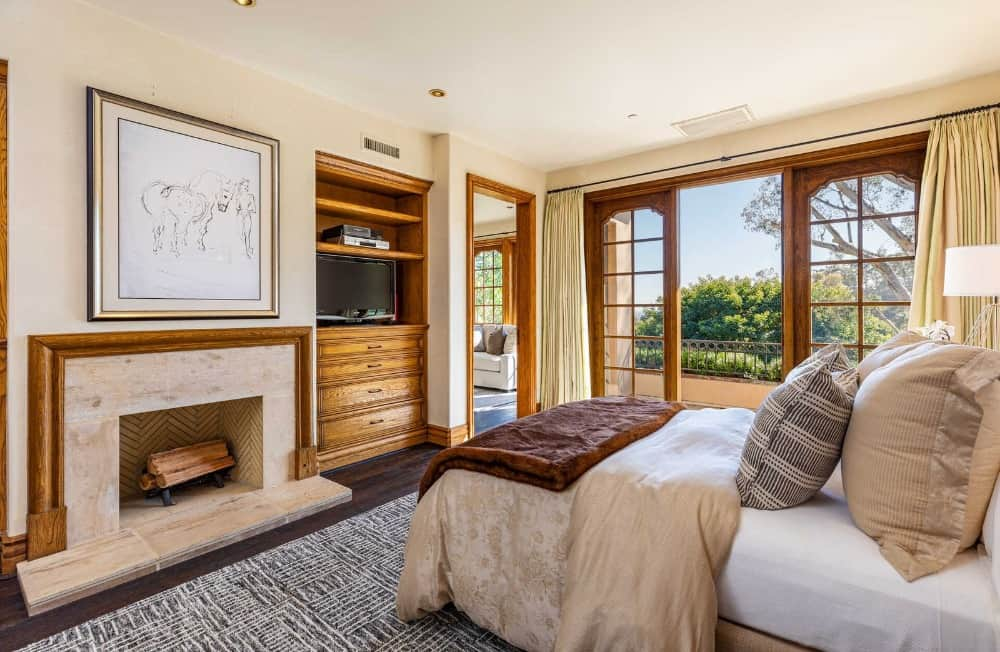 This bedroom suite features a fireplace with a TV set in front of the bed, along with a personal living space. Images courtesy of Toptenrealestatedeals.com.