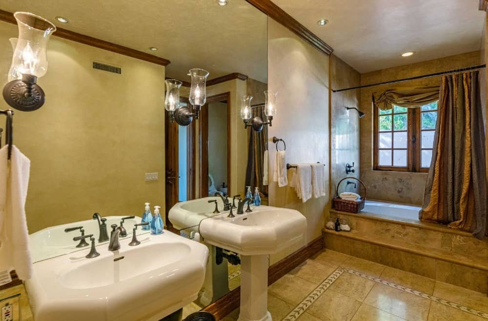 This bathroom also offers two pedestal sinks along with a shower and tub combo on the side. Images courtesy of Toptenrealestatedeals.com.