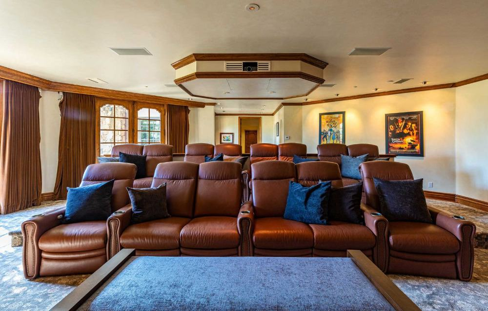 There's a large home theater boasting a set of brown leather sectional seats and stylish carpeted flooring. Images courtesy of Toptenrealestatedeals.com.