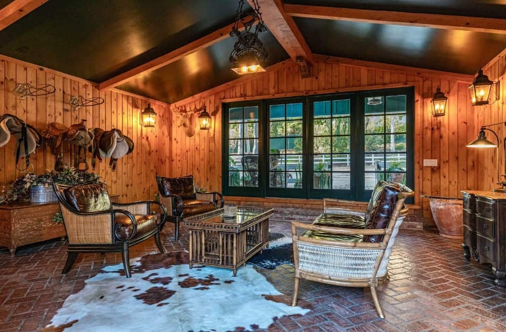 Another look at the large backyard shed with a living space inside featuring wooden walls and warm lighting. Images courtesy of Toptenrealestatedeals.com.