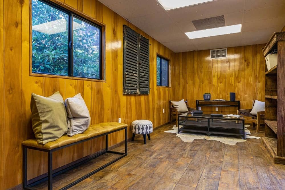 Another one of the living spaces featuring wooden walls and hardwood floors, along with glass windows. Images courtesy of Toptenrealestatedeals.com.