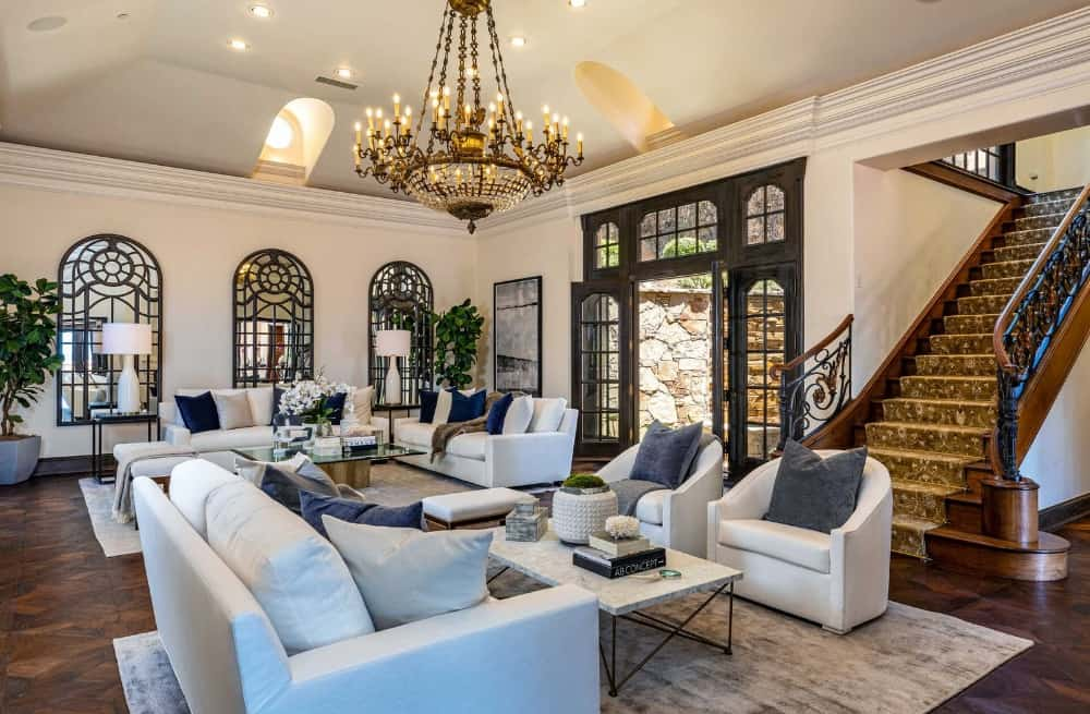 A large living area featuring classy white sofa sets on top of stylish area rugs covering the hardwood flooring. Images courtesy of Toptenrealestatedeals.com.