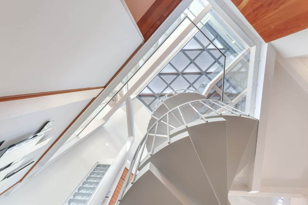 This shot looks up to the house's high custom high ceiling and white spiral staircase. Images courtesy of Toptenrealestatedeals.com.