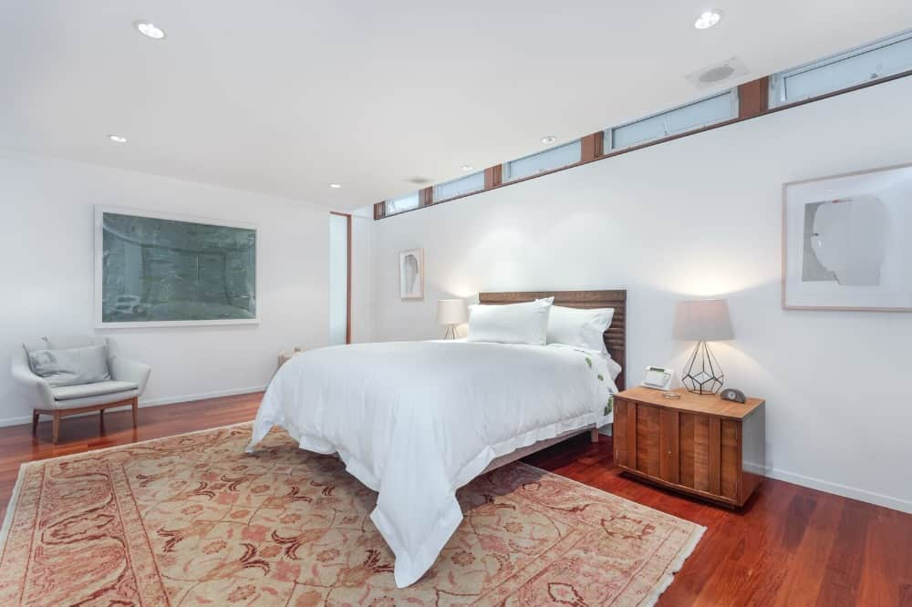 A focused look at this spacious bedroom suite's cozy and modern bed setup lighted by table lamps on both sides. Images courtesy of Toptenrealestatedeals.com.