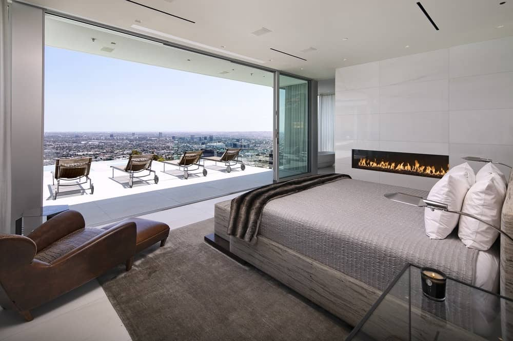 This bedroom has its own modern fireplace beside the gray bed that matches well with the area rug underneath. The whole room is brightened by the wide wall that opens up thanks to sliding glass doors onto a viewing deck that has the perfect view of the city below. Images courtesy of Toptenrealestatedeals.com.