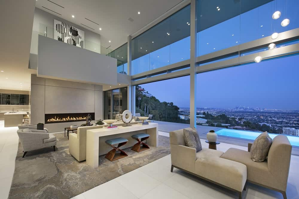 The large and airy living room has a two-story tall glass wall that brings in an abundance of natural lighting as well as provide a sweeping view of the city below. This is augmented by the bright ceiling and bright flooring. Images courtesy of Toptenrealestatedeals.com.