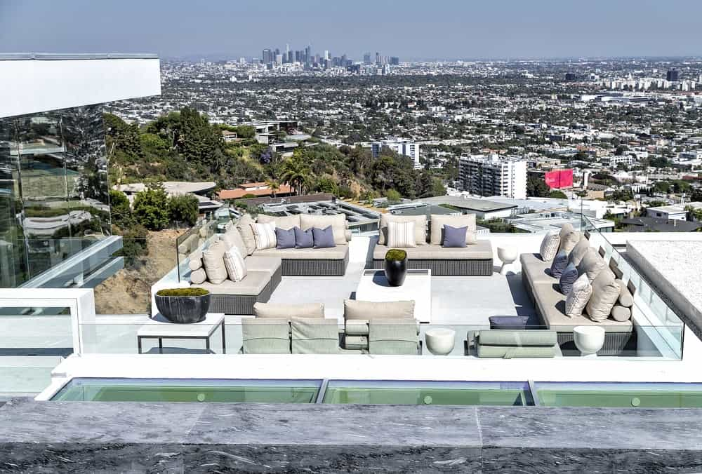 The gorgeous spacious outdoor patio of the house is on one of its terraces fitted with outdoor furniture with cushions. The area is perfect for wine parties and gatherings with the perfect view of the city. Images courtesy of Toptenrealestatedeals.com.