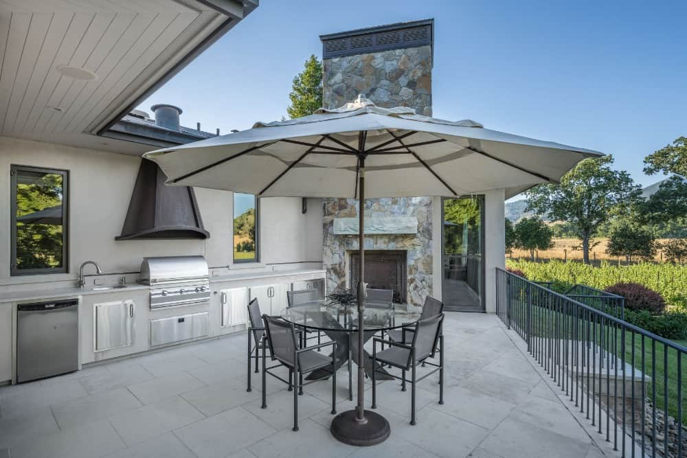 The home also offers an outdoor kitchen featuring a single wall kitchen counter with a fireplace in the corner, along with a round glass dining table set. Images courtesy of Toptenrealestatedeals.com.
