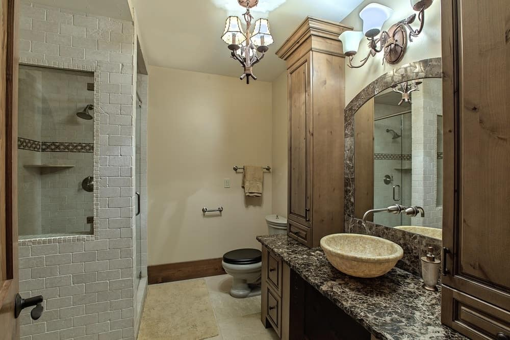 This simple bathroom has a one-sink vanity with a marble countertop that supports the bowl sink across from the walk-in shower area. Images courtesy of Toptenrealestatedeals.com.