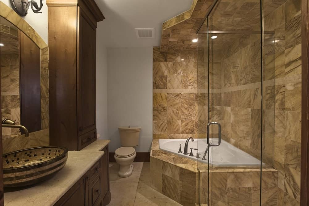 This bathroom has a corner bathtub inlaid with beige marble that extends to the walls as well as the glass-enclosed shower area beside it that is complemented by the dark wooden vanity across. Images courtesy of Toptenrealestatedeals.com.