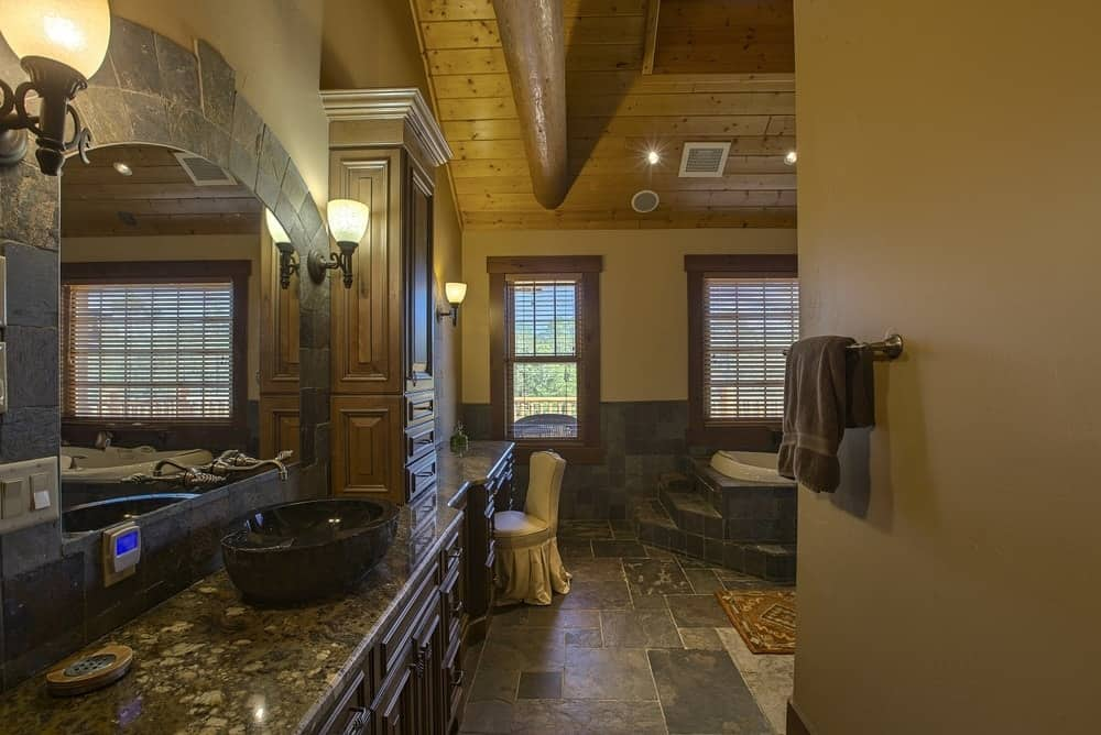 This is a large bathroom with a large vanity and dark bowl sink topped with a wide wall-mounted mirror flanked by charming wall-mounted lamps. This large vanity area sits across from the corner bathtub inlaid with dark stone. Images courtesy of Toptenrealestatedeals.com.