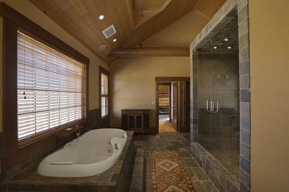 This bathroom has a large porcelain bathtub inlaid with dark stone under the window that brings in an abundance of natural lighting. Images courtesy of Toptenrealestatedeals.com.