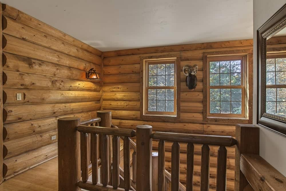 The second floor landing has wooden banisters and railings that match the beautiful wooden log walls with windows and wall-mounted decor. Images courtesy of Toptenrealestatedeals.com.