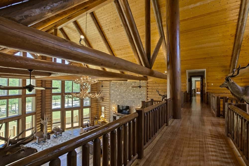 This second floor hallway has waist-high wooden railings for an indoor balcony that looks over the large hall below housing the living room. Images courtesy of Toptenrealestatedeals.com.