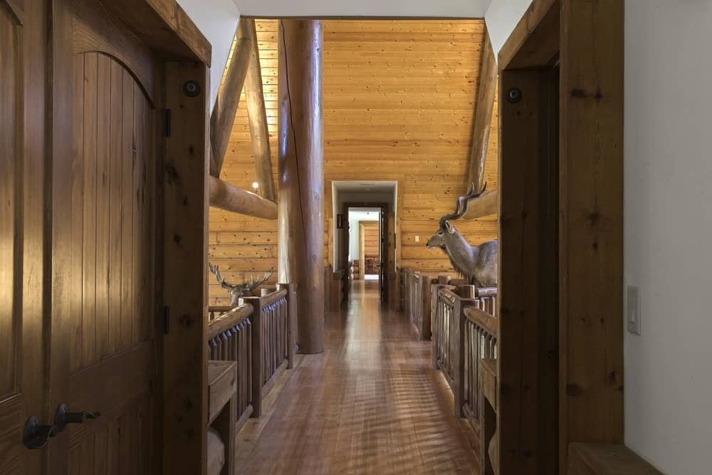 The view from the other end of the hallway shows that it is adorned with a large stuffed animal midway through the wooden hallway. Images courtesy of Toptenrealestatedeals.com.