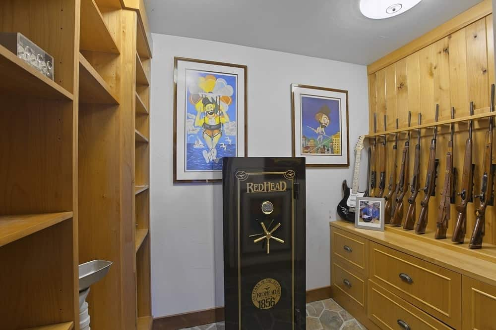 The armory of the house is a hunter's dream with a row of rifles on display across from the large wooden shelving for various other storage. Images courtesy of Toptenrealestatedeals.com.