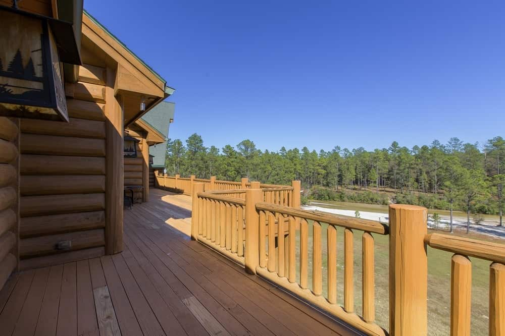 This balcony has a charming wooden walkway that blends well with the wooden railings and wooden log beam exterior walls of the house. Images courtesy of Toptenrealestatedeals.com.