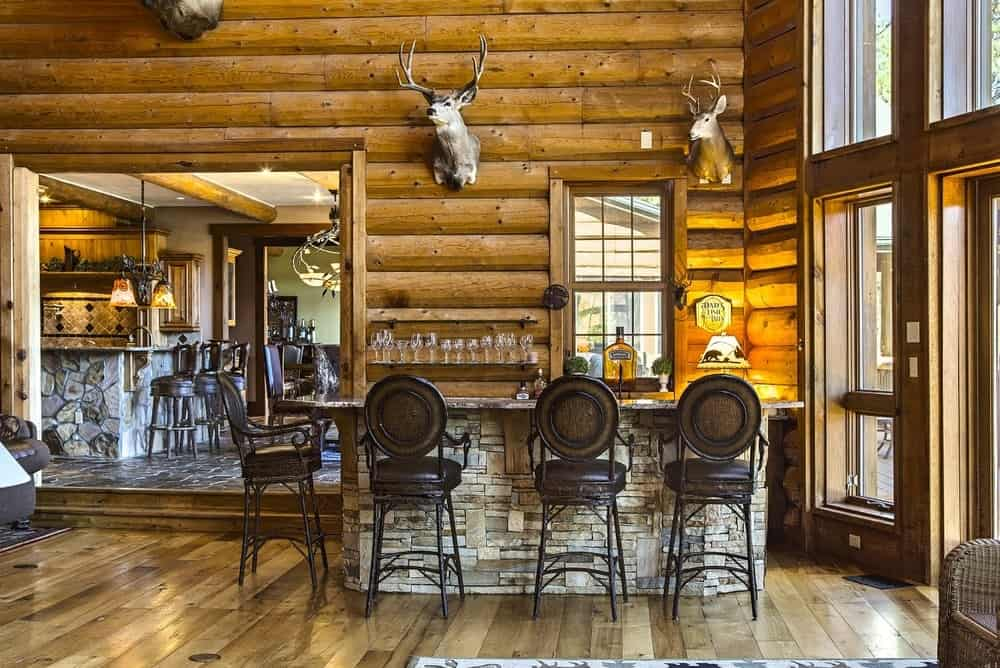 Just across from the living room is the charming bar at the corner with three wrought iron stools facing the rustic stone bar adorned with a couple of stuffed animal heads mounted on the log wall. Images courtesy of Toptenrealestatedeals.com.