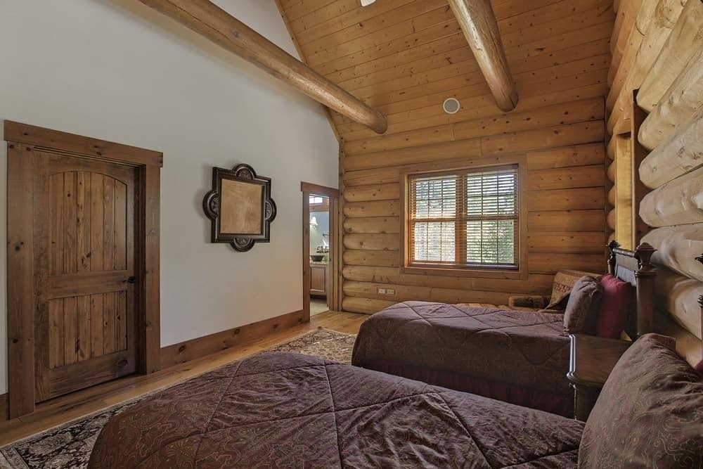 This large bedroom has enough space for two beds with a wooden dresser in the middle and a cushioned arm chair in the corner for a comfortable reading nook. Images courtesy of Toptenrealestatedeals.com.