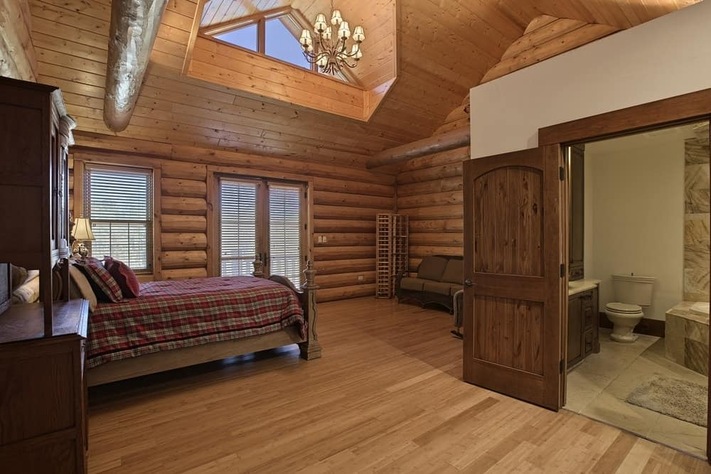 This bedroom is topped with an arched ceiling that has a bright transom window and a simple chandelier for character. There is also a bathroom on the side with charming wooden doors. Images courtesy of Toptenrealestatedeals.com.