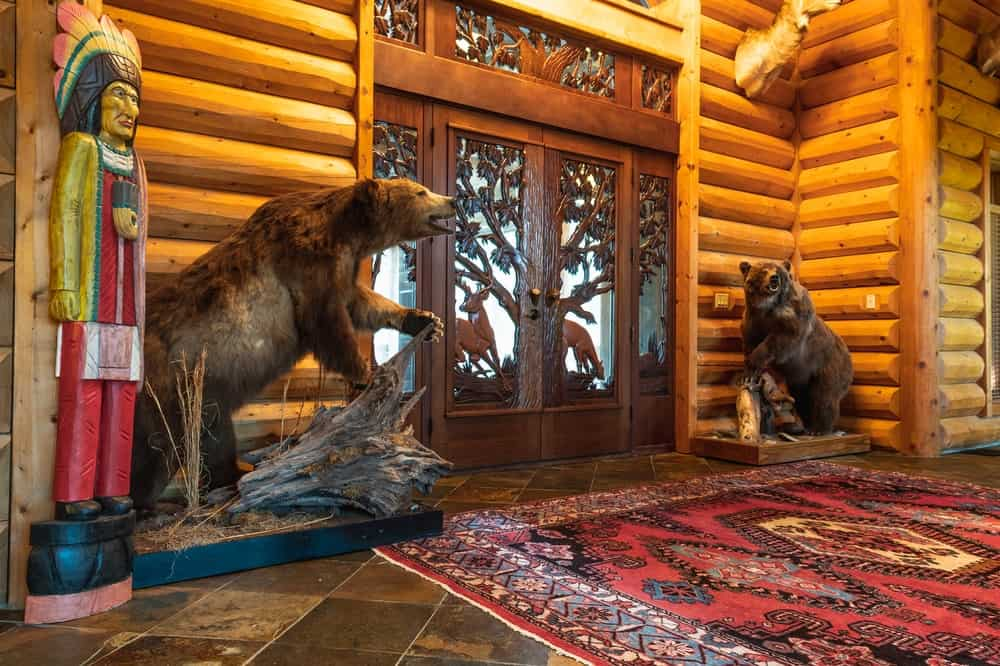 Upon entry, you are welcomed by a beautifully decorated foyer with its detailed and unique front doors flanked by two bears. Images courtesy of Toptenrealestatedeals.com.