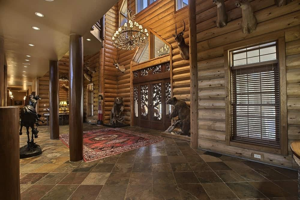 A further view of the foyer shows its large size from its tall ceiling to the floor space dedicated to it adorned with a colorful patterned area rug. Images courtesy of Toptenrealestatedeals.com.