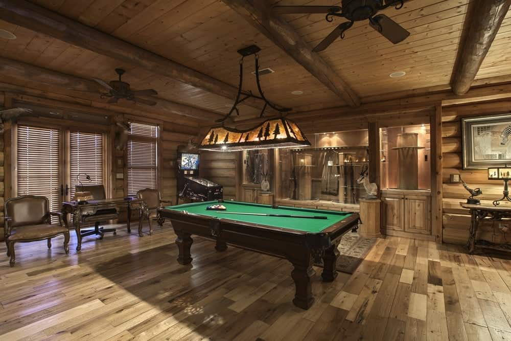 This large log cabin also has a game room with a professional pool table in the middle of the hardwood flooring. This is illuminated by a large lighting hanging from the wooden ceiling through wrought iron support. The beautiful ceiling has exposed wooden log beams and ceiling fans for ventilation. Images courtesy of Toptenrealestatedeals.com.