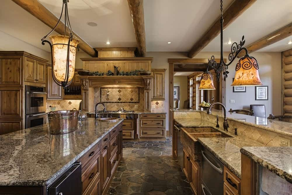 The gorgeous kitchen has the same wooden tone and details as the rest of the log cabin. It has various wooden cabinetry and a galley-style aesthetic with counters topped by charming lamps. Images courtesy of Toptenrealestatedeals.com.