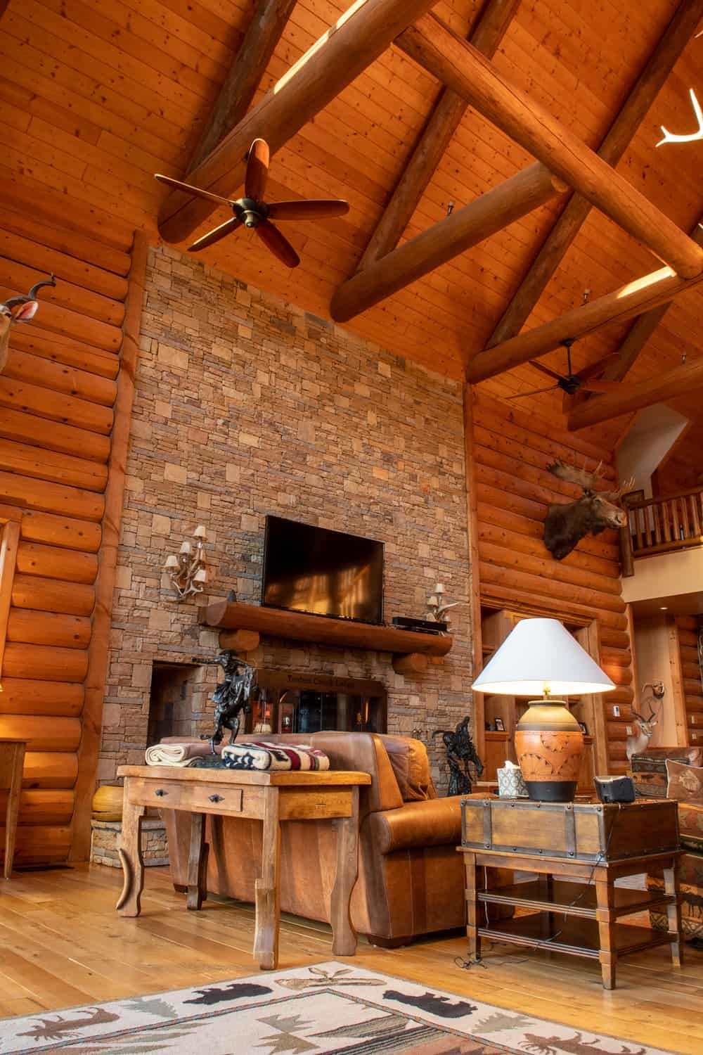 This angle of the living room shows its tall arched ceiling with exposed wooden log beams supporting ceiling fans for ventilation. Images courtesy of Toptenrealestatedeals.com.