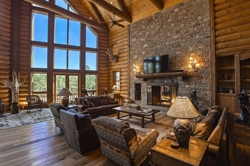 The beautiful Southwestern-style living room has a tall stone wall housing the fireplace with wall-mounted lamps and floating shelves. Images courtesy of Toptenrealestatedeals.com.