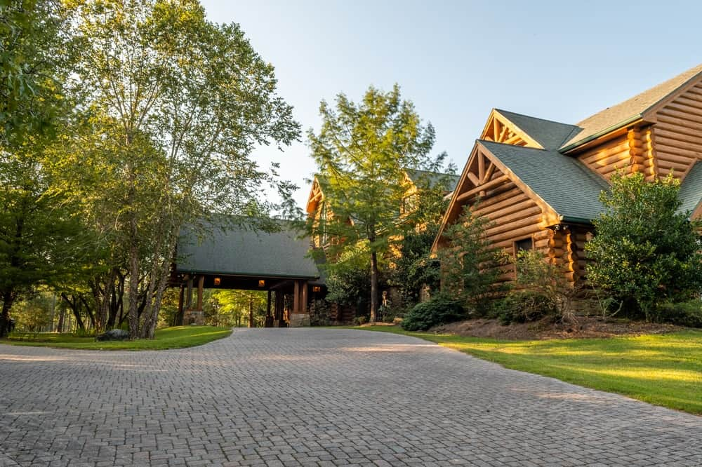 There is a wide driveway towards the main entry of the log cabin with a drop-off point wide enough for a car. From this angle, the entryway is framed the by the lush and tall trees of the landscaping. Images courtesy of Toptenrealestatedeals.com.