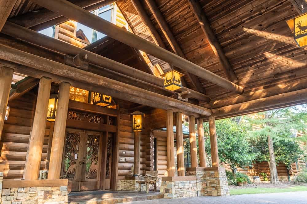 The craftsmanship and architecture of the large cabin is on full display with this close-up shot of the entryway complemented by warm lanterns. Images courtesy of Toptenrealestatedeals.com.