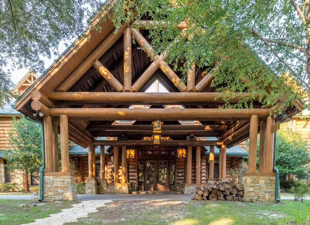 A front view of the main entryway and drop-off point of the log cabin shows just how large the house is. This entryway sets the mood and serves as a teaser for the rest of the house with its log beams and tall ceiling. Images courtesy of Toptenrealestatedeals.com.