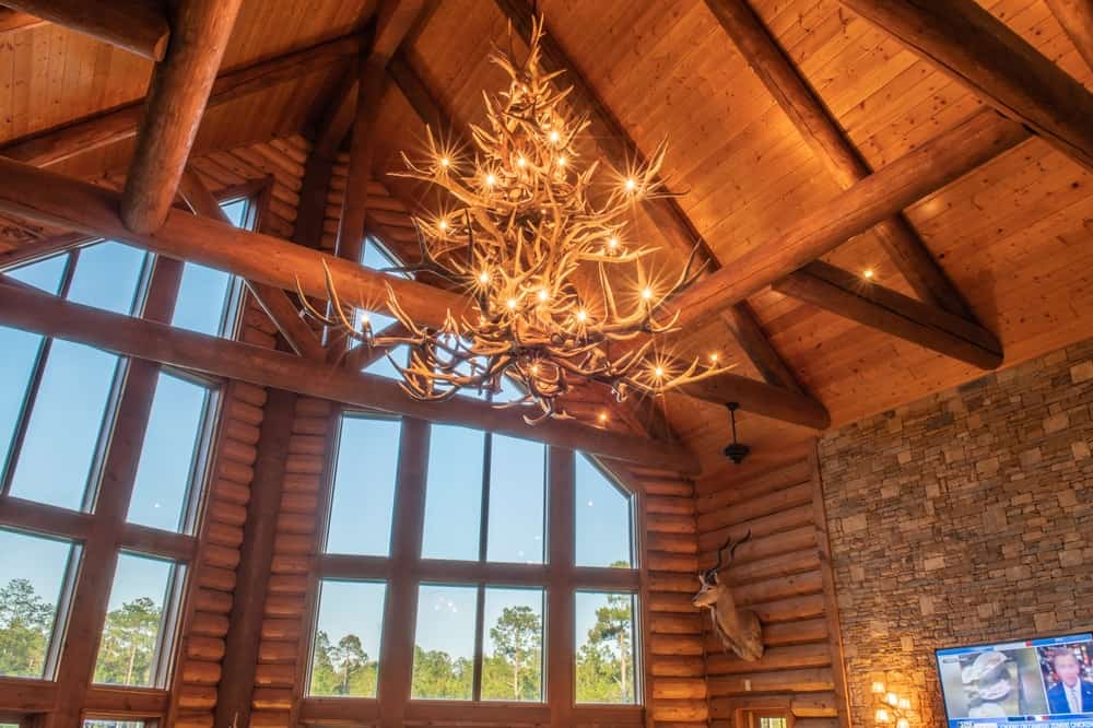A closer look at the chandelier reveals that it is made of antlers for a distinct Southwestern-style feel complemented by the warm yellow lights that give the wooden arched ceiling a warm glow along with its exposed wooden log beams. Images courtesy of Toptenrealestatedeals.com.