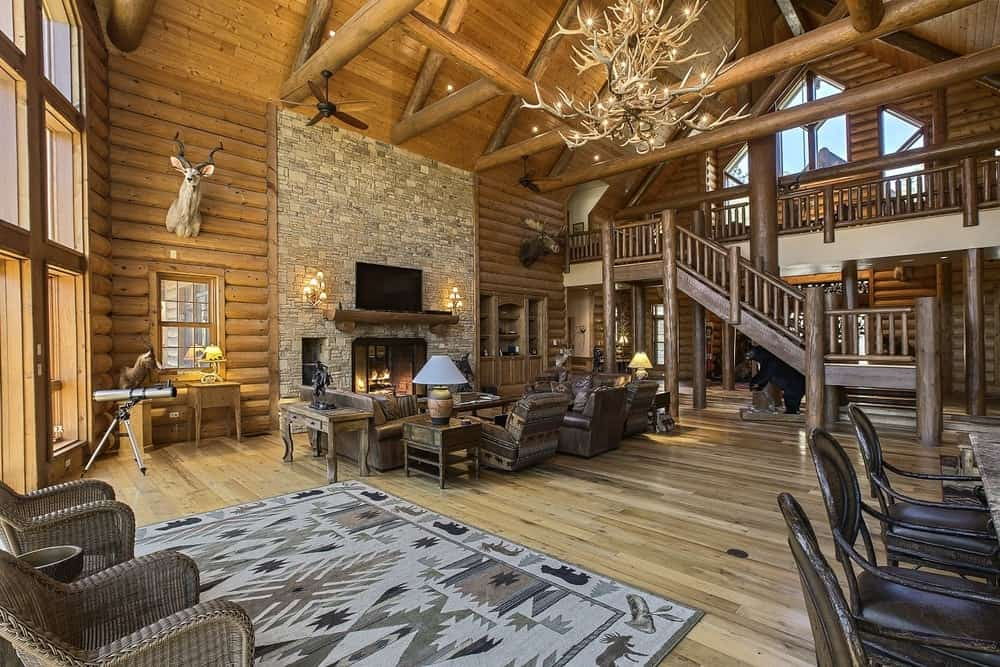 This large hall is complemented by a majestic chandelier hanging from the middle of the tall arched ceiling with exposed log beams. Images courtesy of Toptenrealestatedeals.com.