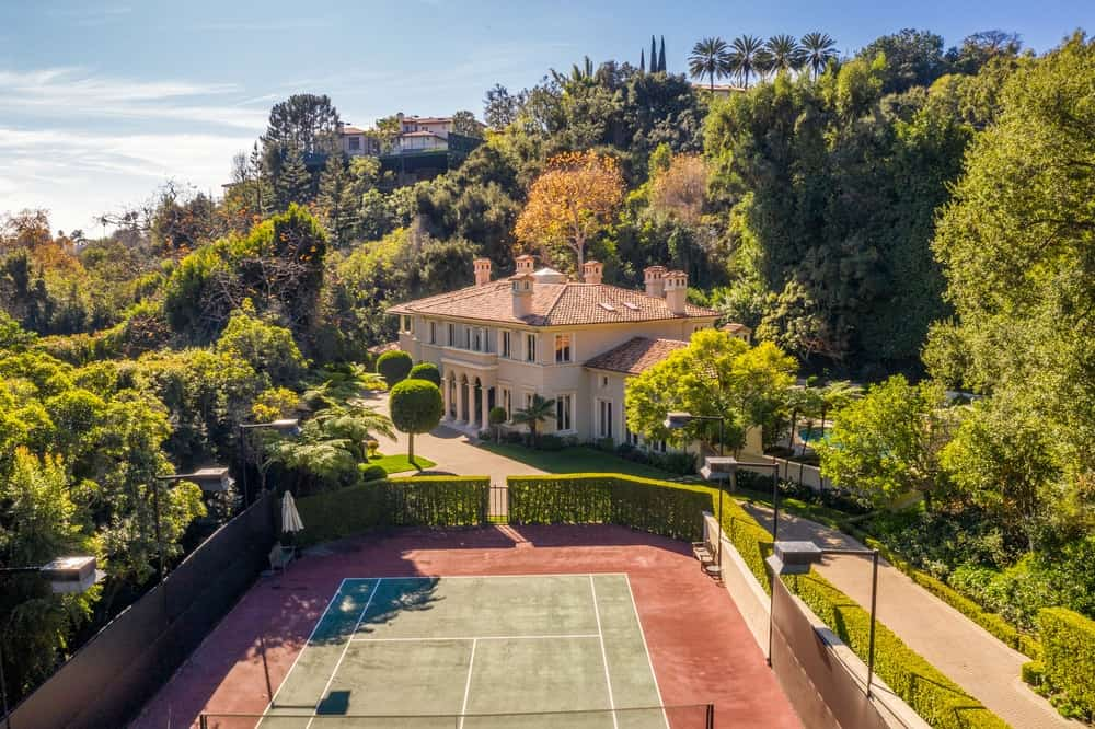 This aerial shot of the house shows all the outdoor areas of the property. There is the tennis court beside the driveway and the pool on the far distance as well as the imposing mansion that is beautifully framed by the tall trees in the background. Images courtesy of Toptenrealestatedeals.com.