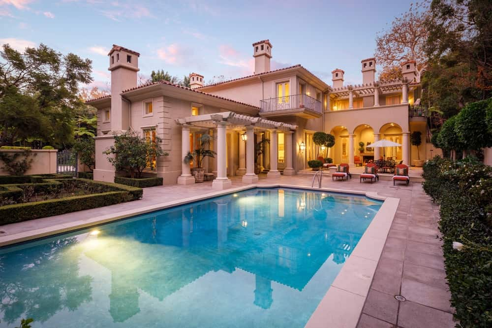 This view of the house from the backyard shows that it has a large luxurious swimming pool surrounded by terracotta tiles on its walkways. This complements the beige exteriors of the mansion adorned with a trellis-topped walkway on one side leading to an outdoor dining area as well as lawn chairs facing the pool. Images courtesy of Toptenrealestatedeals.com.