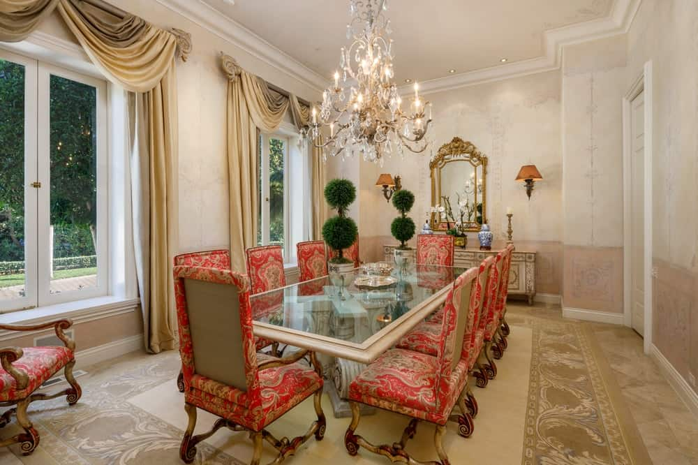 This amazing formal dining room has a large elegant rectangular glass-top dining table that is surrounded by upholstered dining chairs with a red tone to stand out against the beige walls and ceiling that hangs a majestic chandelier over the middle of the table. Images courtesy of Toptenrealestatedeals.com.