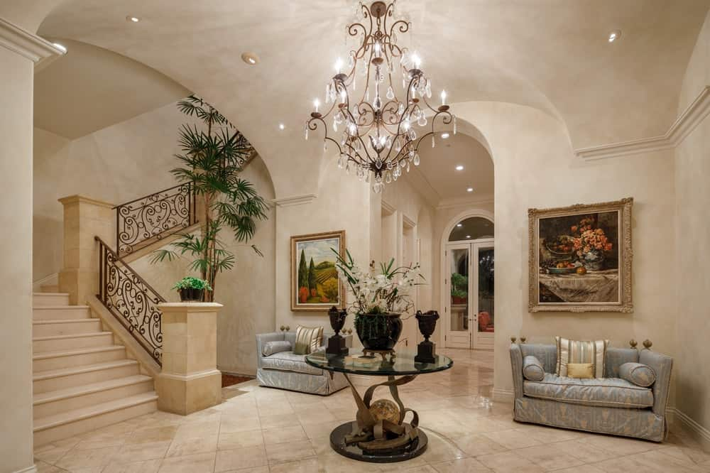 This grand foyer has a spacious beige flooring with a round glass-top display table in the middle paired with a pair of comfortable cushioned gray arm chairs flanking one of the tall archways with each chair adorned by a wall-mounted painting above. Images courtesy of Toptenrealestatedeals.com.