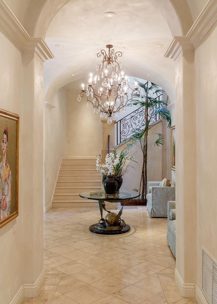 This view of the foyer from one of the hallways shows that the area is illuminated by a majestic decorative chandelier hanging over the round glass table in the middle of the foyer. The staircase leading to the second level is also visible from this point. Images courtesy of Toptenrealestatedeals.com.