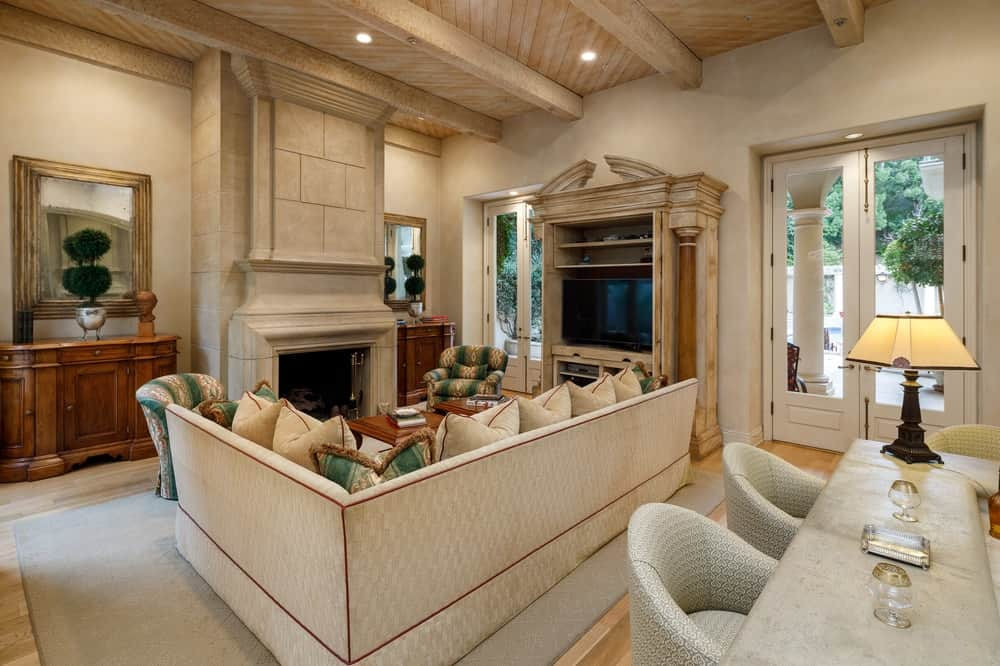 The gorgeous living room is dominated by a large L-shaped sofa filled with matching beige pillows and accented by a few green ones. On one side of the sofa is the large wooden structure that houses the TV placed against one of the beige walls flanked by glass doors. Images courtesy of Toptenrealestatedeals.com.