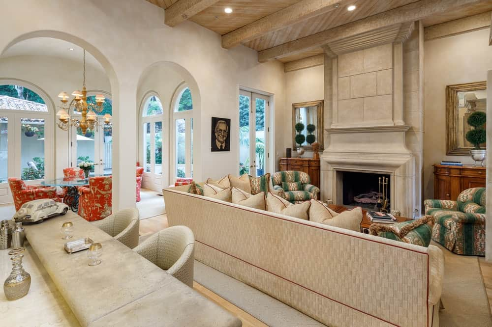 In front of the L-shaped sofa is the large beige stone pillar that houses the gorgeous warm fireplace reaching to the beige ceiling that has exposed wooden beams. Behind the sofa is the breakfast bar with light-toned stools and a marble countertop. Images courtesy of Toptenrealestatedeals.com.