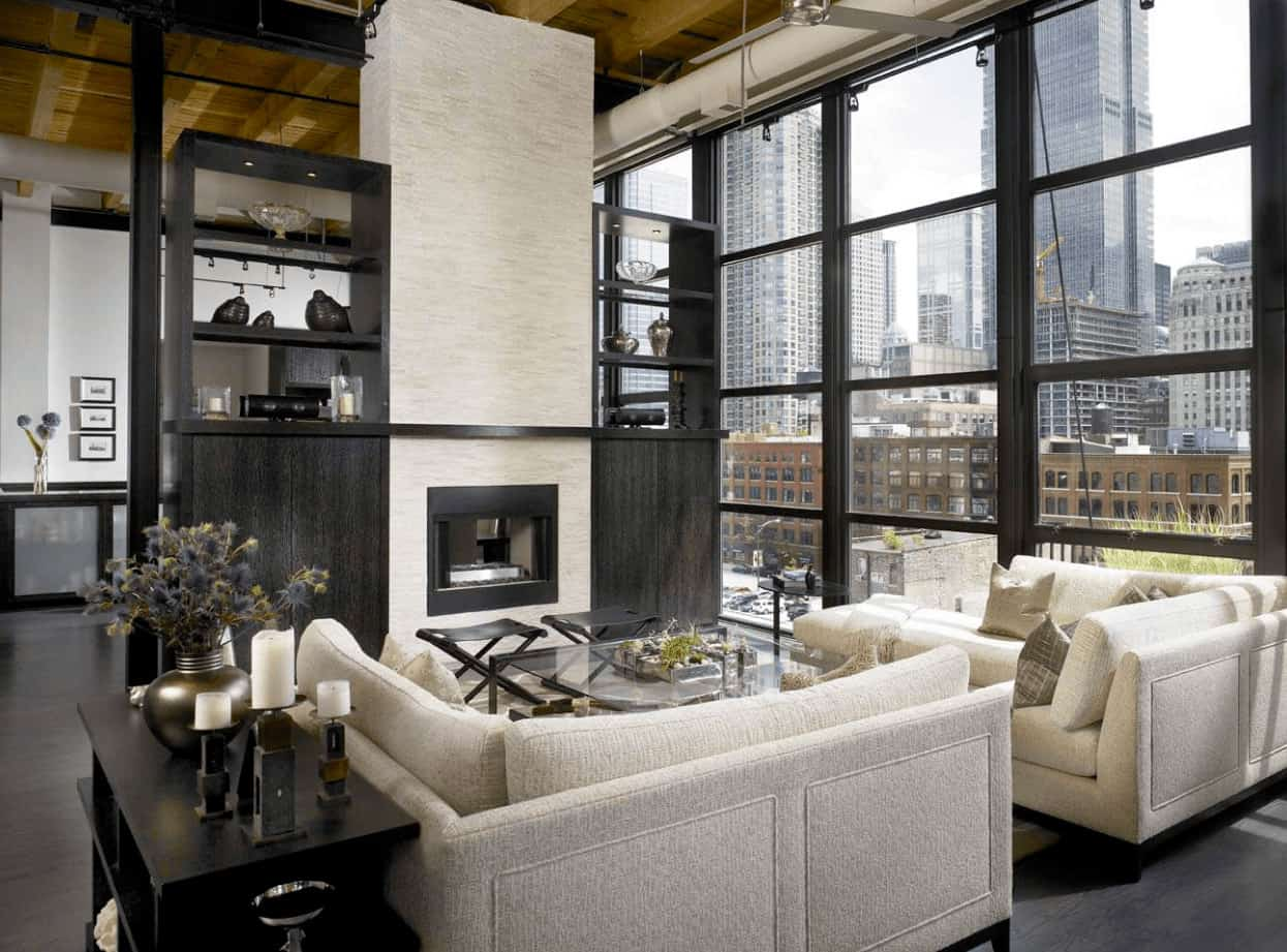 The bright living room showcases floor to ceiling glass windows lined with track lights. It includes a fireplace fixed to the beige pillar in between black storage shelves.