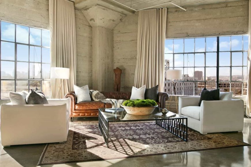 This living room boasts metal-framed glass windows covered with beige draperies and concrete flooring topped by a large patterned rug. It is furnished with brown chesterfield sofa and white armchairs paired with a glass top coffee table.